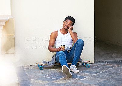 Buy stock photo Shot of a young skater sitting on his skateboard and talking on his cellphone