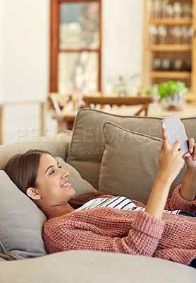 Buy stock photo Shot of a young woman lying on her sofa using a digital tablet