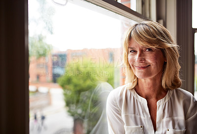 Buy stock photo Portrait of a smiling mature woman sitting by a window at home