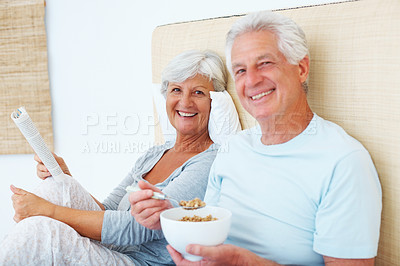 Buy stock photo Portrait of senior couple sitting on bed and smiling with woman reading a book and man having breakfast