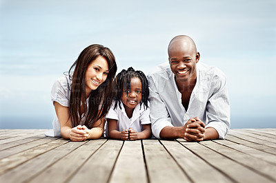 Buy stock photo Portrait of a young family lying on a boardwalk outside