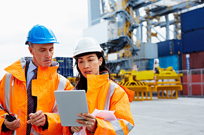 Buy stock photo Shot of two dock workers looking at a tablet while standing in a dockyard