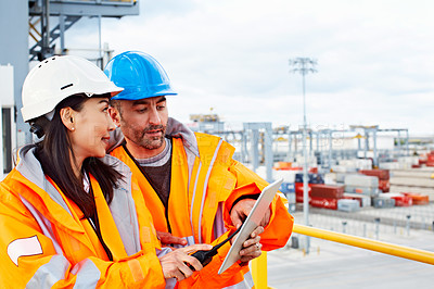 Buy stock photo Shot of two workers talking together over a digital tablet while standing on a commercial dock