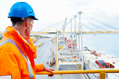 Buy stock photo Shot of a man in workwear standing on a walkway looking out over at a large commercial dock
