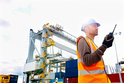 Buy stock photo Shot of a young man in workwear talking on a walkie talkie while standing on a large commercial dock
