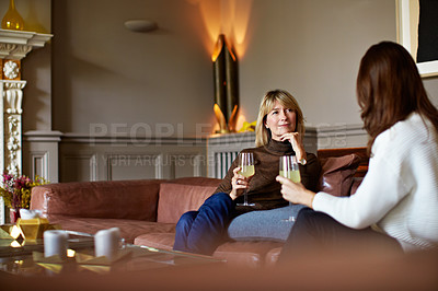 Buy stock photo Shot of a woman drinking wine while talking with her daughter on the living room sofa