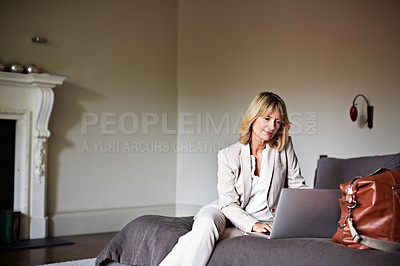 Buy stock photo Shot of a mature businesswoman using her laptop while sitting on her hotel bed