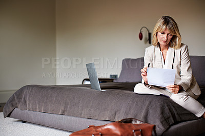 Buy stock photo Shot of a mature businesswoman going over some paperwork while sitting on her hotel bed
