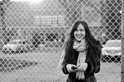 Buy stock photo Black and white shot of a young woman using her phone while standing against a mesh wire fence