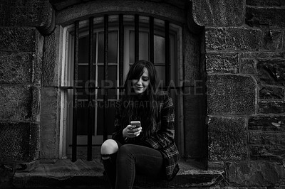 Buy stock photo Black and white shot of a young woman sitting outside on a window sill while using her cellphone
