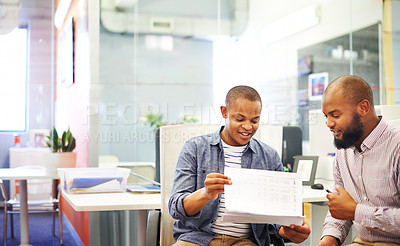 Buy stock photo Shot of two colleagues discussing plans in a modern office