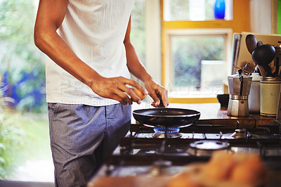 Buy stock photo Cropped shot of a man making fried eggs for breakfast