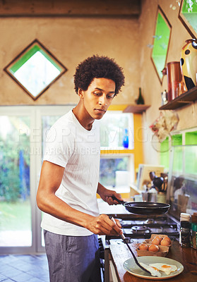 Buy stock photo Shot of a young man making fried eggs for breakfast