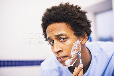 Buy stock photo Shot of a young man shaving in the bathroom