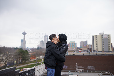 Buy stock photo Shot of a happy young couple sharing a romantic kiss out in the city