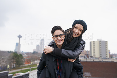 Buy stock photo Shot of a happy young couple enjoying a piggyback ride out in the city
