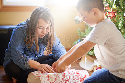 Buy stock photo Shot of a brother and sister wrapping Christmas presents at home