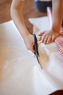 Buy stock photo Cropped shot of a little boy wrapping Christmas presents at home