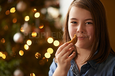 Buy stock photo Portrait of a young girl eating Christmas cookies at home