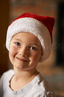 Buy stock photo Portrait of a happy little boy wearing a santa hat at home on Christmas
