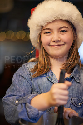 Buy stock photo Shot of a happy young girl baking at home during Christmas