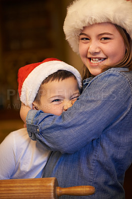 Buy stock photo Shot of a young brother and sister playfully hugging while baking at home during Christmas