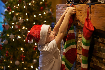 Buy stock photo Shot of a little boy hanging up Christmas stocking at home