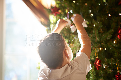 Buy stock photo Shot of a little boy decorating a Christmas tree at home