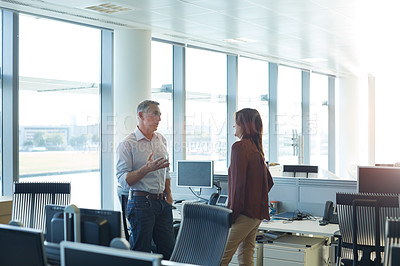 Buy stock photo Shot of two people talking together while standing in an office