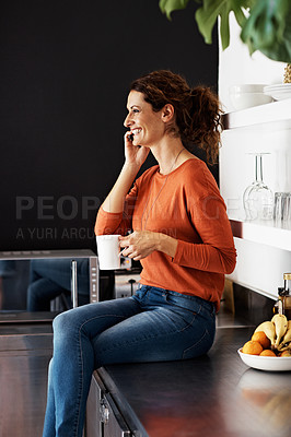 Buy stock photo Shot of a woman sitting on her kitchen counter drinking a coffee and talking on the phone