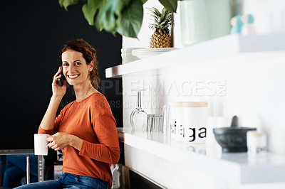 Buy stock photo Portrait of a woman sitting on her kitchen counter drinking a coffee and talking on the phone