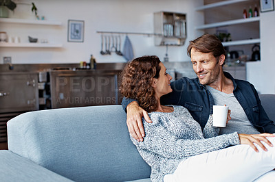 Buy stock photo Shot of a content mature couple sitting on their living room sofa drinking coffee