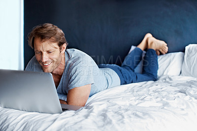 Buy stock photo Shot of a mature man lying on his bed using a laptop