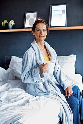 Buy stock photo Portrait of a mature woman sitting on her bed drinking a coffee