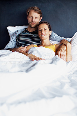 Buy stock photo Portrait of a smiling mature couple lying in bed