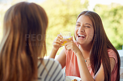 Buy stock photo Shot of two friends eating breakfast together on a balcony