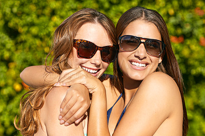 Buy stock photo Shot of two friends in bikinis hugging each other and laughing