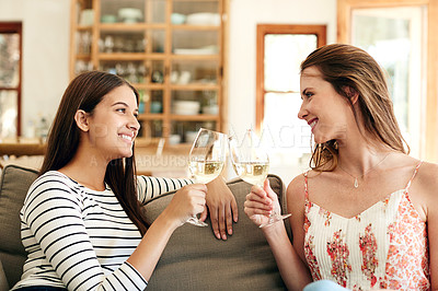 Buy stock photo Shot of two friends talking together and drinking wine while sitting on the sofa at home