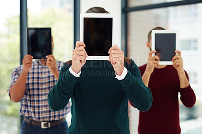 Buy stock photo Cropped shot of a group of businesspeople standing with their tablets over their faces
