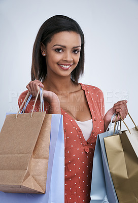 Buy stock photo Studio shot of a woman holding shopping bags against a gray background
