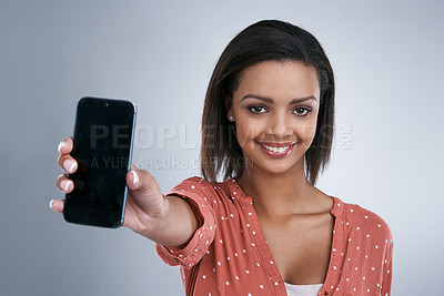 Buy stock photo Shot of a young woman showing you her cellphone