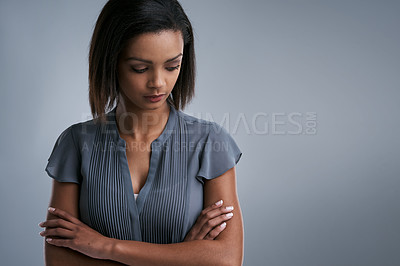 Buy stock photo Studio shot of a young woman looking sad against a gray background