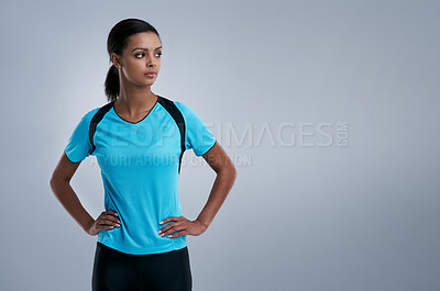 Buy stock photo Studio shot of a sporty young woman posing confidently against a gray background