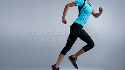 Buy stock photo Studio shot of a fit woman running against a gray background