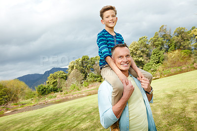 Buy stock photo Portrait of a dad giving his son a piggyback outside