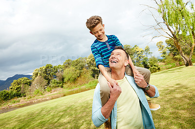 Buy stock photo Shot of a dad giving his son a piggyback outside