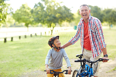 Buy stock photo Portrait of a father and son riding bicycles in a park