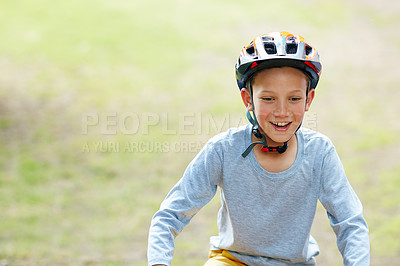 Buy stock photo Shot of a smiling boy riding his bicycle