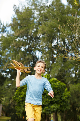 Buy stock photo Shot of a young boy running through a park with a toy airplane