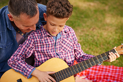 Buy stock photo Shot of a father teaching his son how to play guitar while sitting outside